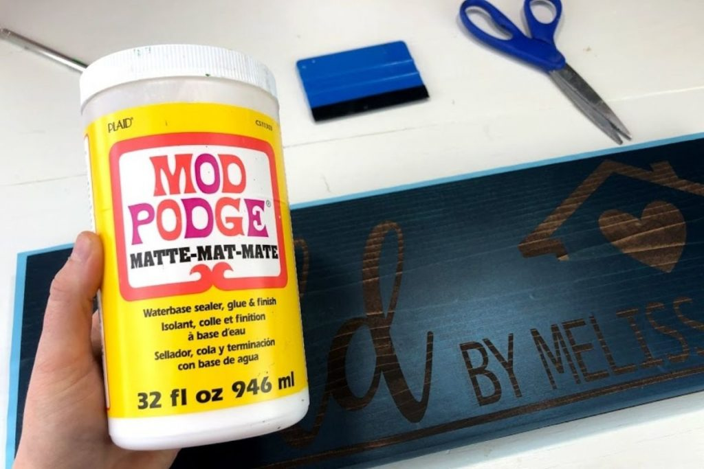woman holding a large bottle of matte finish mod podge to seal a wood sign stencil. Sign base is stained in a dark kona brown. There is a blue vinyl squeegee and a blue handled pair of scissors on the craft table