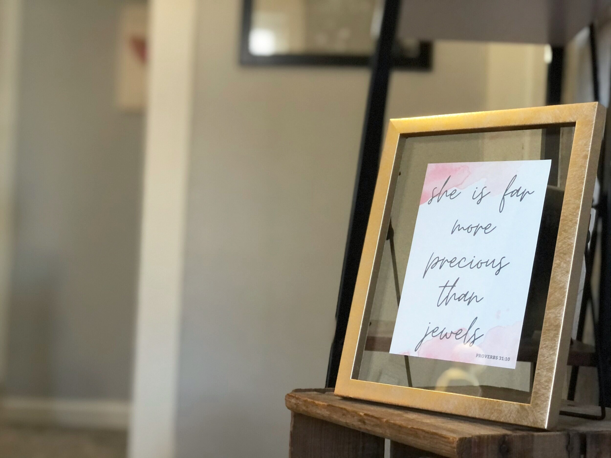 Gold picture from with a watercolor print out of she is far more precious than jewels bible verse. Pink and blush colored watercolor marks