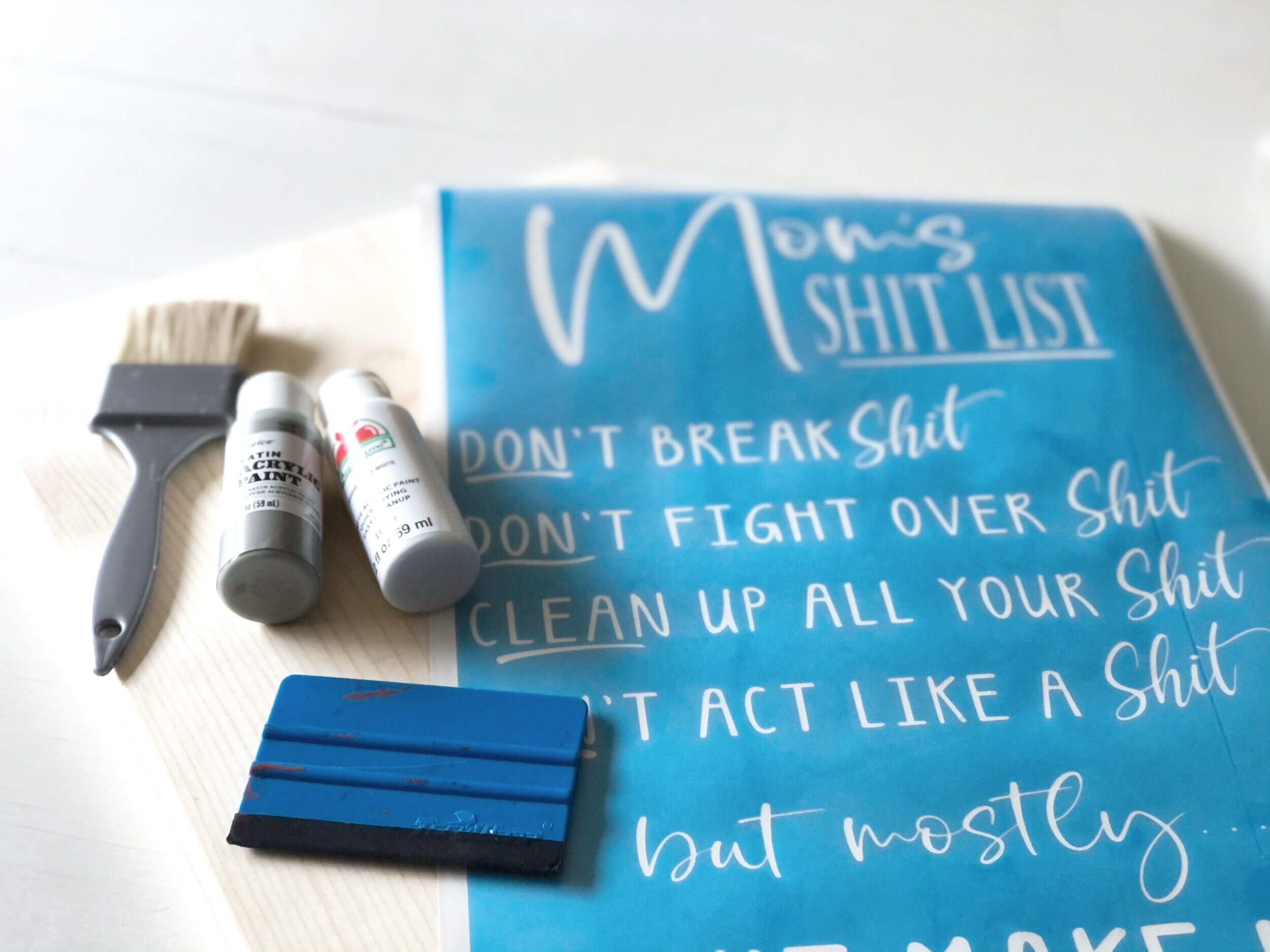 supplies needed to make a humorous mom wood sign. Gray and white acrylic paint bottles, blue vinyl squeegee, wide paint brush, oramask blue translucent stencil, clear transfer tape, natural wood base