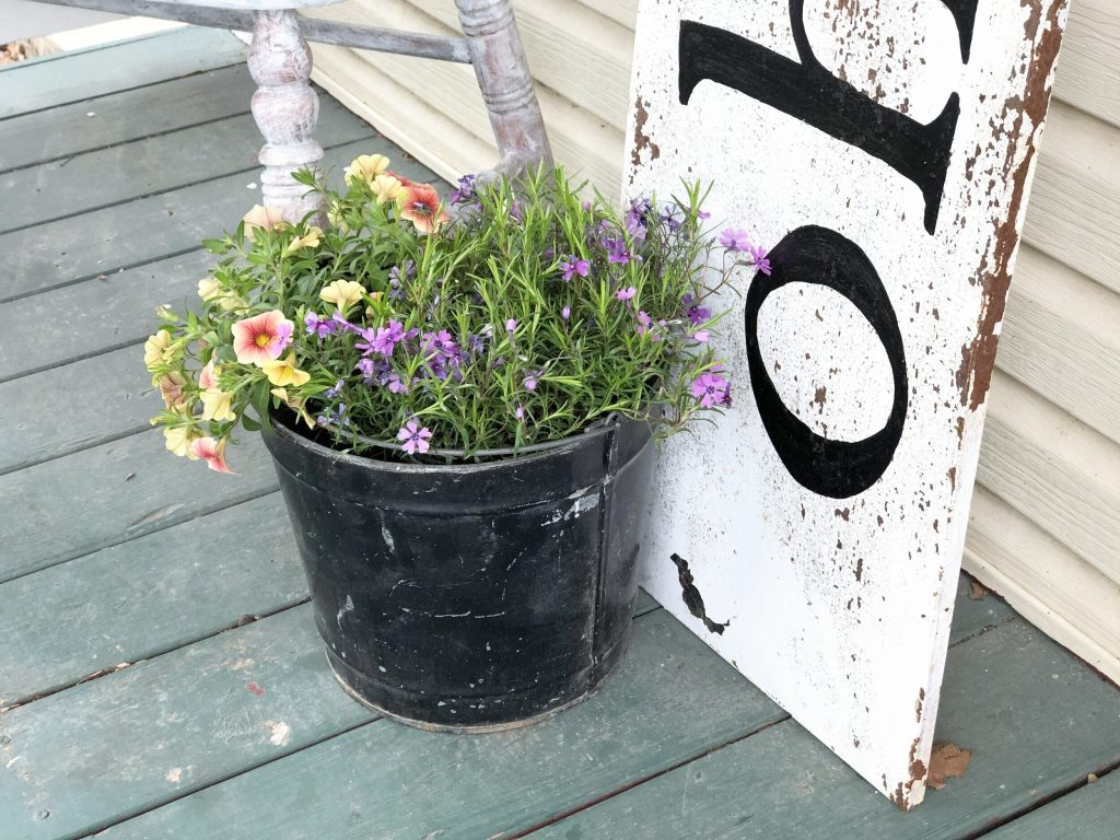 chippy paint metal white porch sign. Black metal bucket propped at the bottom of the welcome porch sign. Bucket is filled with purple and yellow flowers. Porch is painted in a dark green.