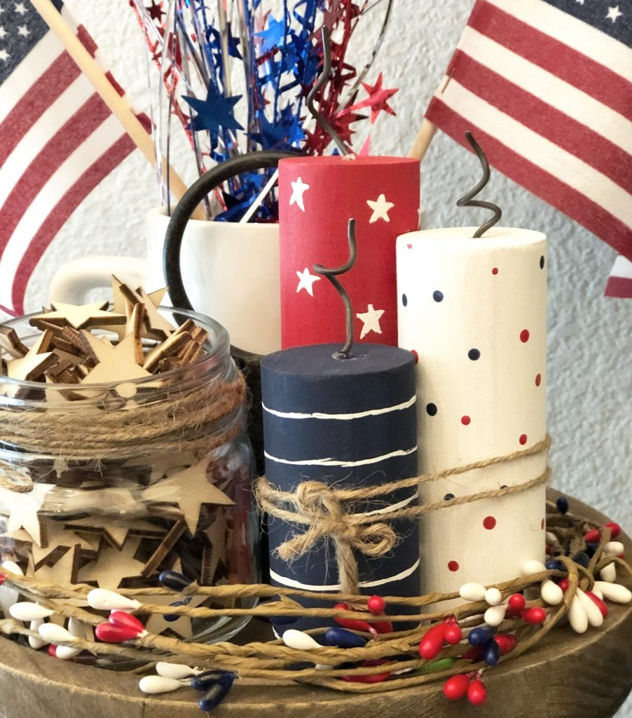 Red, white, and blue mini wood firecrackers on a rustic farmhouse tiered tray. White firework with red and blue polka dots. Navy blue firecracker with hand painted white stipes. Red firecracker with hand painted white stars. Wrapped in twine with metal rustic wire wicks. Unfinshed wood stars in a mason jar American flag