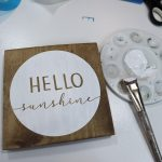 Light colored stained wood sign that says hello world. White painted circle around the lettering. Paintbrush and paint tray next to the wood sign that has white paint on the tray and paint bristles.