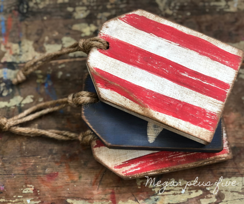 set of three 4th of July wood tags. Top tag is white with red stripes. Hole in the top center of wooden tag with a piece of twine used for a hanger. Under the striped tag there is a painted blue tag with a white star. Tags are distressed with sandpaper and antiquing wax.