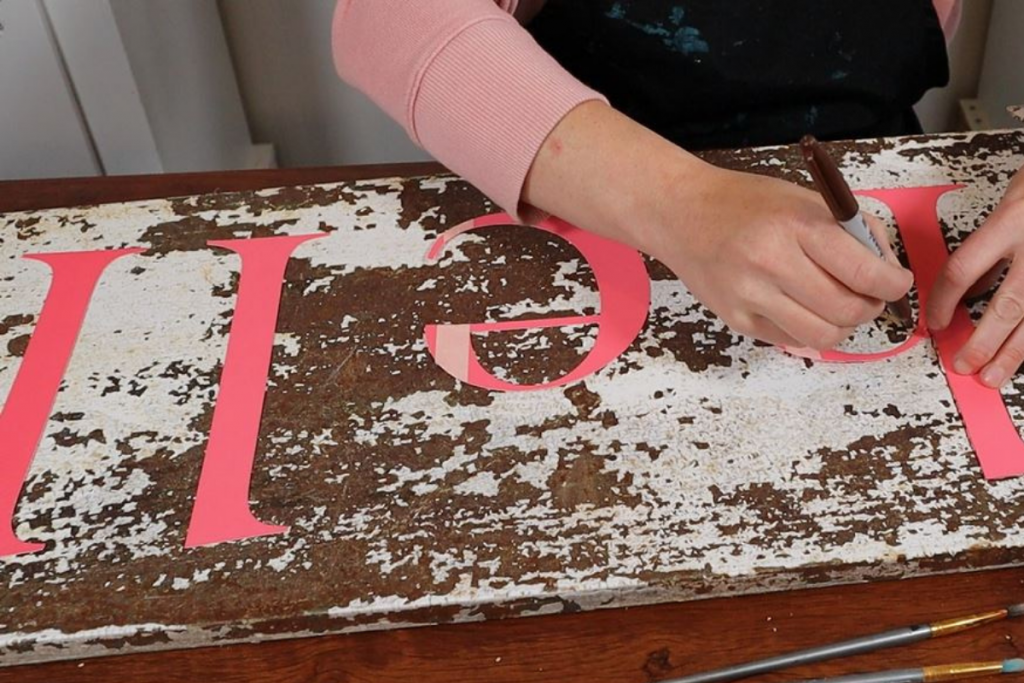 woman is using a sharpie to trace red cardstock letter cutouts onto an old rusty white chipped paint metal locker door to make a sign. There is a bottle of black outdoor paint on the craft table and two artist paintbrushes