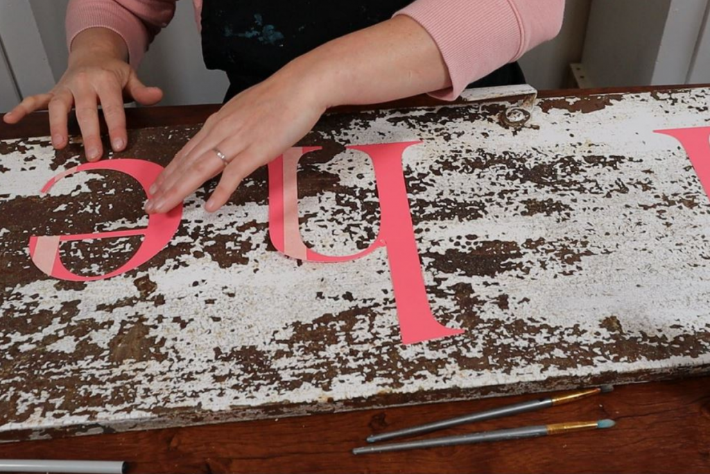woman is arranging cardstock letter cutouts on a rusty white chipped paint metal locker door to make a painted lettered sign