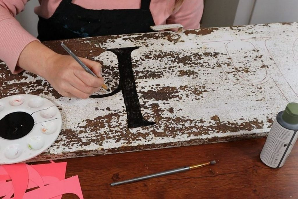 woman is using black outdoor paint to paint inside the traced lines of letters onto a rusty white chipped paint metal locker cabinet door. She is using an artist paintbrush and has a paint tray with black paint in the center. Pile of cardstock letter stencils on the craft table.