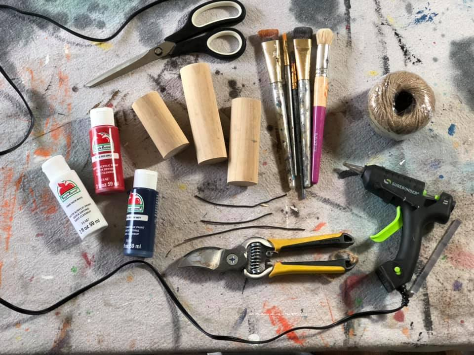 Craft materials needed for DIY firecrackers. Wood dowel rod pieces, scissors, paint brush, twine, red acrylic paint, white acrylic paint, blue acrylic paint, hot glue gun, wire cutters, rustic wire, drop cloth background