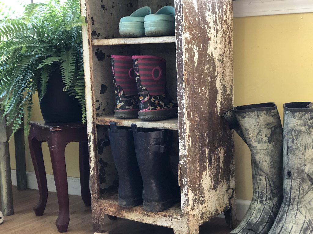 old chipped paint rusty vintage locker repurposed into a mudroom shoe organizer. There are 3 pairs of mud rain boots, pair of blue crocs, red table with a fern. Walls are painted yellow and floor is hardwood