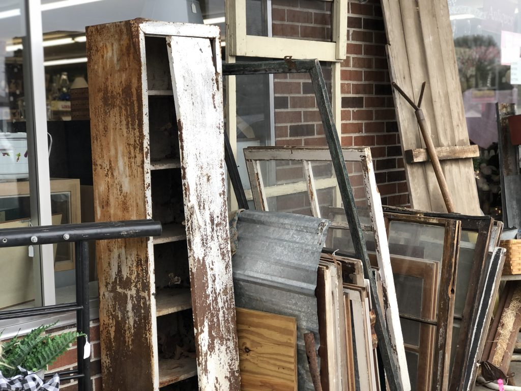 sidewalk sale at an antique store storefront. Rusty white chipped paint metal locker, old windows, old fence panel, brick wall behind the vintage items.