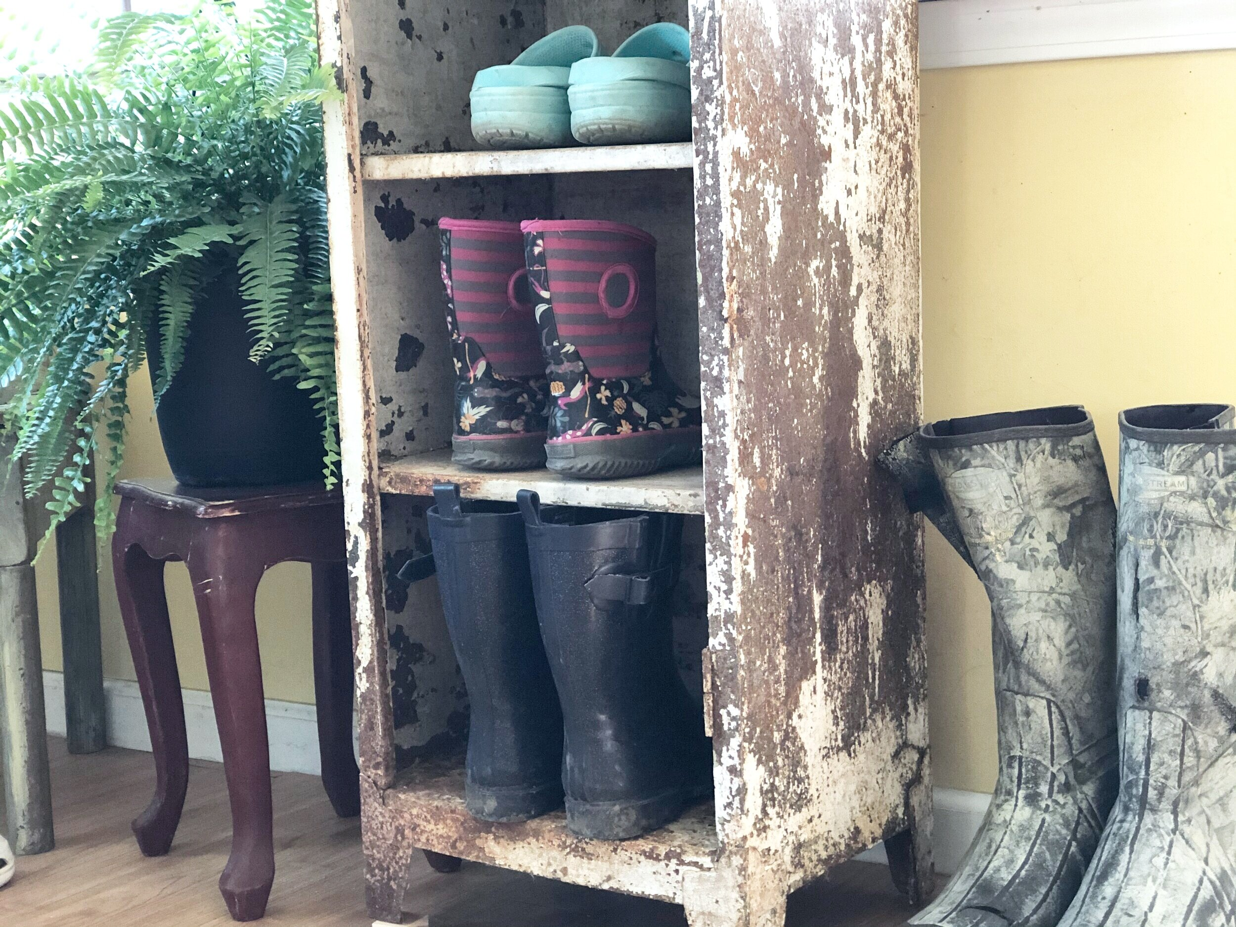 metal cabinet with chipped paint and rust turned into a shoe holder for a mud room. Shoe organizer is holding dark blue sparkly rain boots, child's stripped and floral rainboots, light blue crocs. Beside the metal cabinet are camouflaged hunting water boots and a red table with a green fern.
