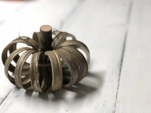 rusty pumpkin made from mason jar rings. Stick for the stem and the canning jar rings are gathered in a circle around the stick to make it look like a pumpkin.