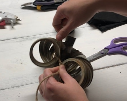 Making a rusty farmhouse pumpkin from canning mason jar metal rings. String the canning lids on a piece of twine the curve them around a stick to form a circle. Then tie the twine in a knot.