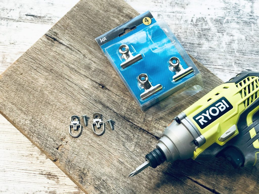 Ryobi drill with a drill bit, picture hanging hardware, push pin office supply clips from the dollar tree, scrap piece of barn wood on a weathered white washed background