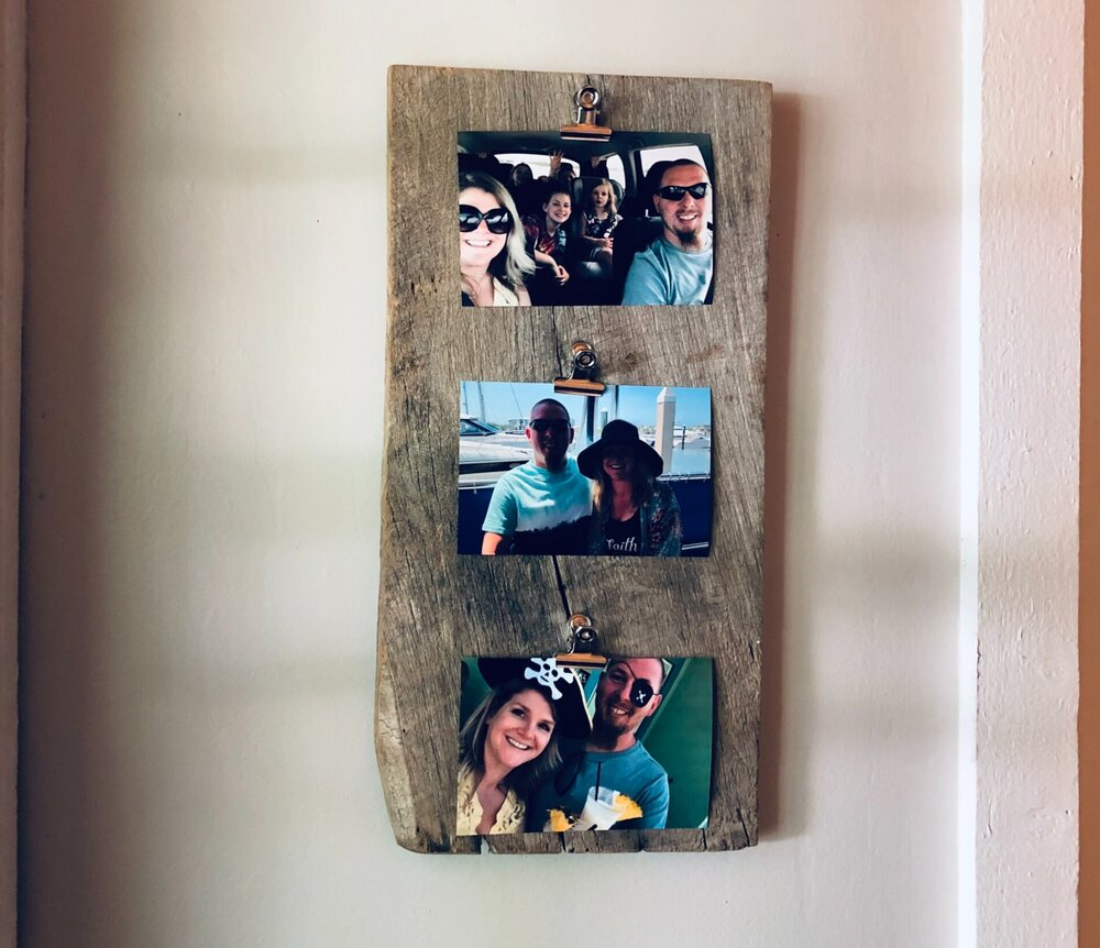Set of 3 three colored photos hanging vertically on a reclaimed weathered piece of bard wood. On a mast bedroom light gray tan wall for a simple personalized look for a room.