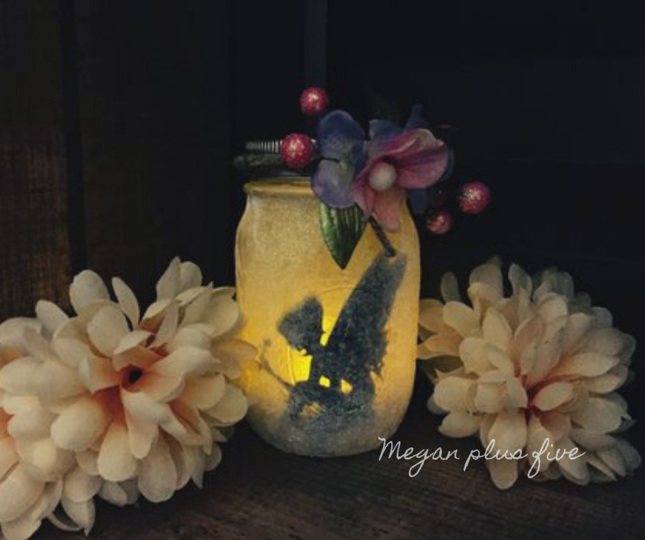 Learn how to make this glowing light-up fairy jar lantern. Smooth clear mason jar is covered is extra fine white glitter to give a whimsical effect. Fairy like accent flowers have been glued to the top of the mason jar. There are two large flowers on either side of the glowing silhouette fairy jar.