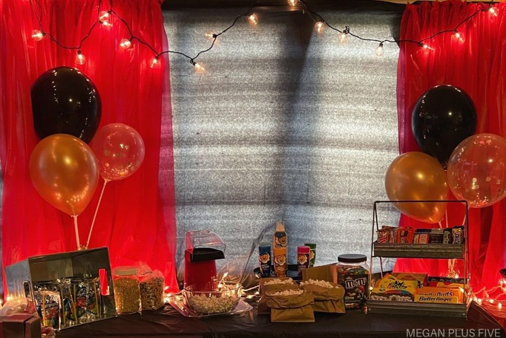 movie theatre snack table. Hanging outdoor bulb lights, lights on the table, gold and black balloons on sticks in vases, theatre candy, popcorn, popcorn seasonings, black and red theatre curtains, juicy drinks,