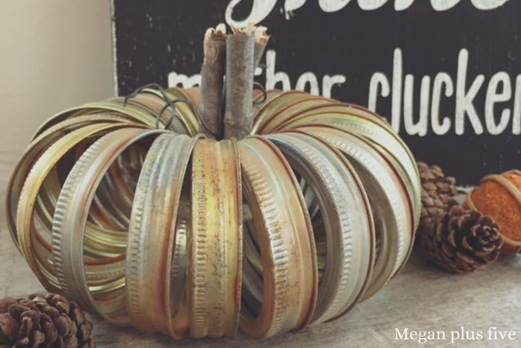 rusty canning jar rings used to make a rustic farmhouse pumpkin decoration. Several mason jar rings forming a circle with a stick in the middle acting as the stem. Two pieces of rustic baling wire coming out of the middle of the fall metal pumpkin.