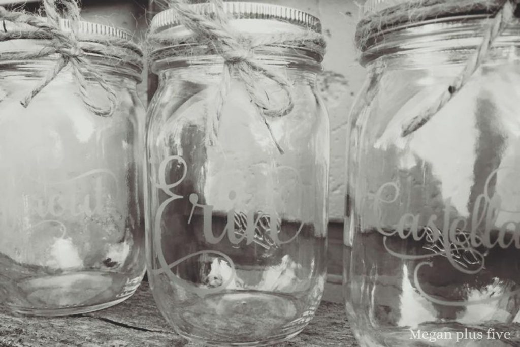black and white picture of personalized etched names on a clear mason jar. Jars have a piece of twine wrapped around the lip of the glass jars.