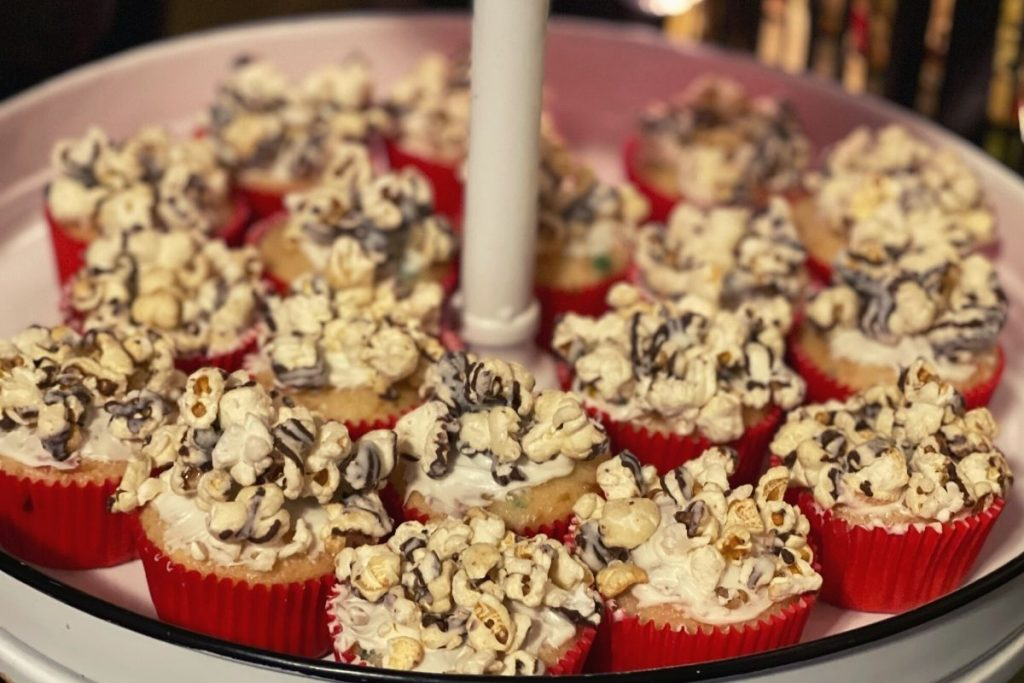 cupcakes with red liners topped with popcorn to look like theatre popcorn. Cupcakes are sitting on a white enamel tiered tray.