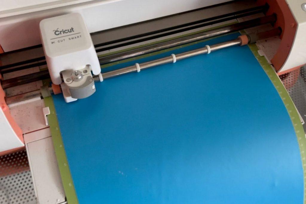 Cricut cutting machine cutting out a stencil on a green cutting mat. Stencil is blue translucent oramask material.