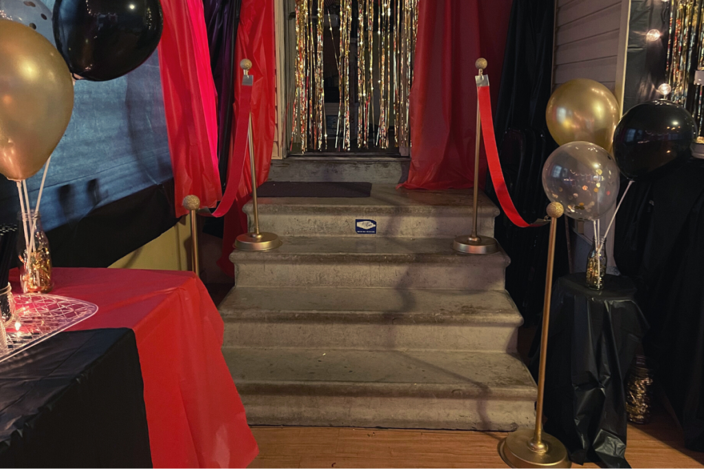 movie theme party, theatre themed movie party with a homemade red carpet stanchions going up the stairs. Gold doorway fringe curtain with black and red curtains, black and gold balloons on the party table and bulb lighting