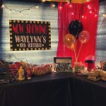 movie themed birthday party setup. NOW SHOWING Waylynn's 10th birthday party black, red, yellow, and white birthday sign. Party tables have a hot dog machine, black, gold, and clear confetti gold balloons in a vase. Black and red curtains covering the windows, popcorn bar with flavored seasoning, popcorn popper machine, full size candy bars and boxes of candy.