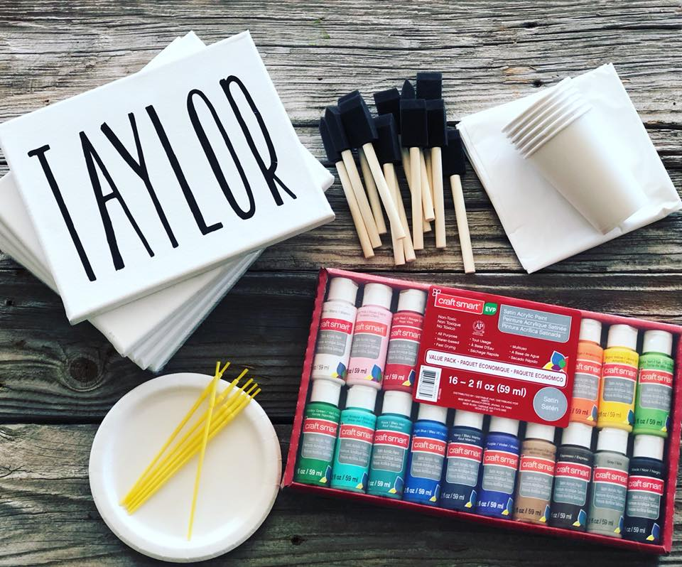 """Stack of canvases to make personalized name art. The top white canvas reads, TAYLOR, in black matte finish vinyl. There are a group of wooden handled 1"""" sponge brushes, stack of white paper cups, a white vinyl table cloth, pack of assorted acrylic paints, yellow kids paint brushes, a stack of white paper plates. This is kid's DIY craft kit."""