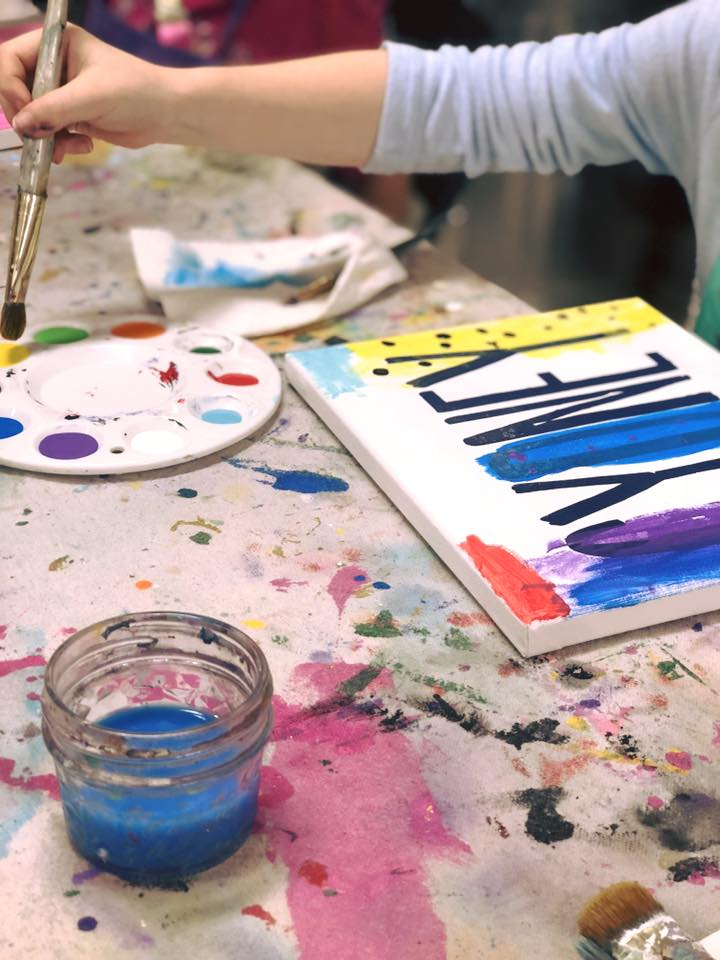 Child painting a white canvas with their name on the canvas in black lettering. Paint pallet with the colors purple, green, red, yellow, dark blue, and light blue. A cup of water for the paintbrush, paint covered paper towel. A canvas drop cloth to protect the table surface from acrylic paint stains.