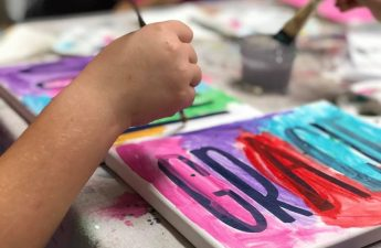 Child painting their name, Gracie, on a white canvas with the colors pink, purple, red, and teal. They are using a small paintbrush. Letters are made from black vinyl.