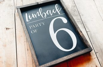 black wooden sign with dark brown stained frame. lettering is painted in font and has a personalized last name at the top of the sign and party of 6 underneath. Sign is sitting on a pallet background.