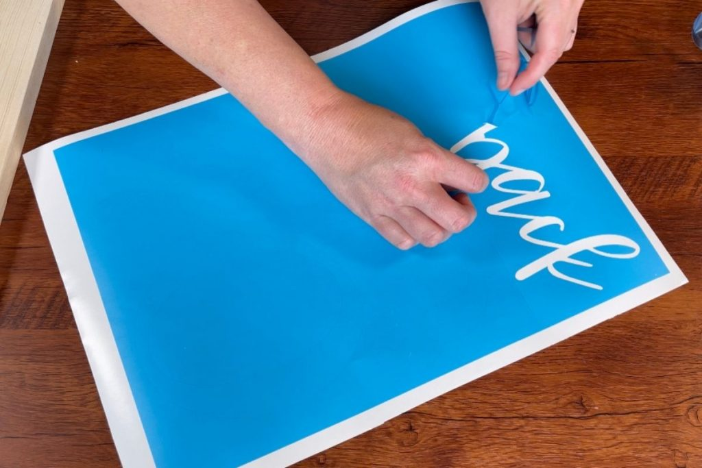 woman is weeding a blue translucent Oramask stencil using a sewing pin. Lettering is in cursive and at the top of the stencil material.
