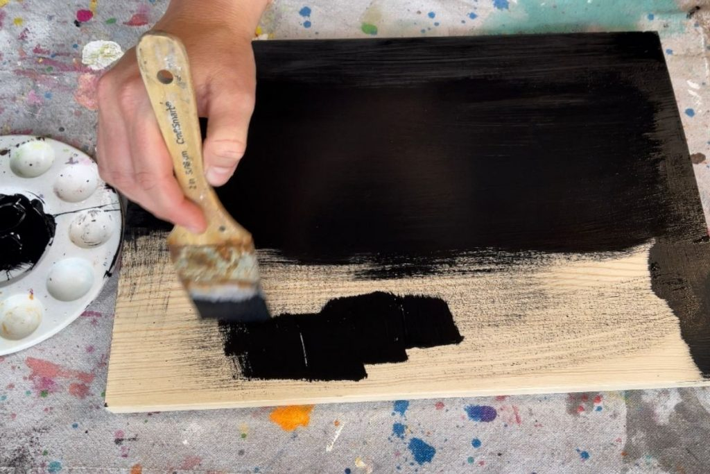 """woman painting a 1""""x12"""" wood sign base black using a 2"""" artist craft paintbrush. There is a paint tray beside the wooden base with black acrylic paint in the center. Woman is using a canvas drop cloth to protect her table surface while she crafts."""