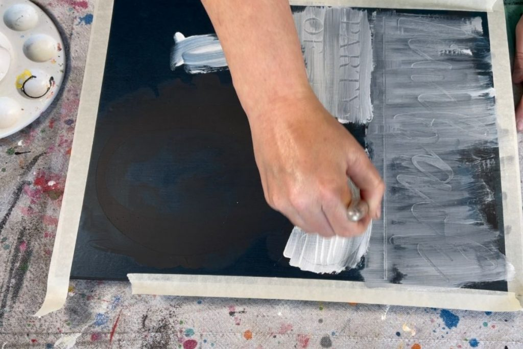 woman is using a paintbrush to paint a stenciled wood sign with white acrylic paint. Lettering at the top of sign is in cursive font. She is painting a thin layer and you can see the wood grain through the first coat of paint.