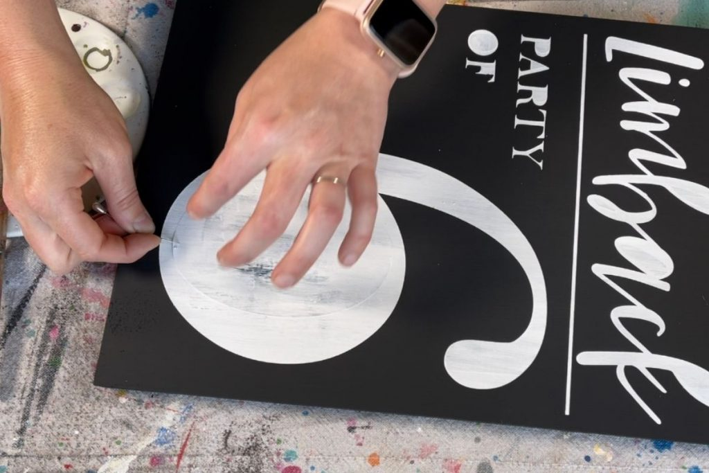 woman is using a large sewing pin to peel up the middle pieces from a personalized stencil. Sign is painted in black and lettering is painted in white.
