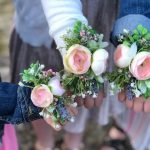 3 little girls wearing wrist corsages made from fake flowers. Each corsage has 2 blush colored rosettes, lavender sprigs, lambs ear, and babies breath. Girls are dressed up for a father daughter dance. 2 are wearing dark colored jean jackets and another is wearing a white cardigan. The girls are standing outside on green grass.