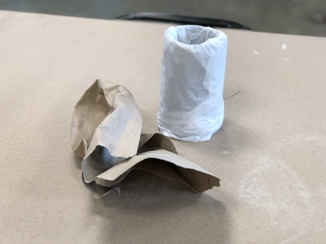adding thick brown builders or craft paper to the inside of a glass mason jar to absorb the shocking from shipping. Glass jar is wrapped in tissue paper and there is a crumpled up brown piece of paper next to the jar.