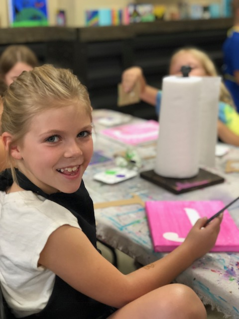"""smiling little girl painting an 8""""x10"""" canvas pink. There is a painted letter J in the middle of the canvas. On the craft table there is a roll of paper towels and assorted craft supplies for kids canvas art painting."""