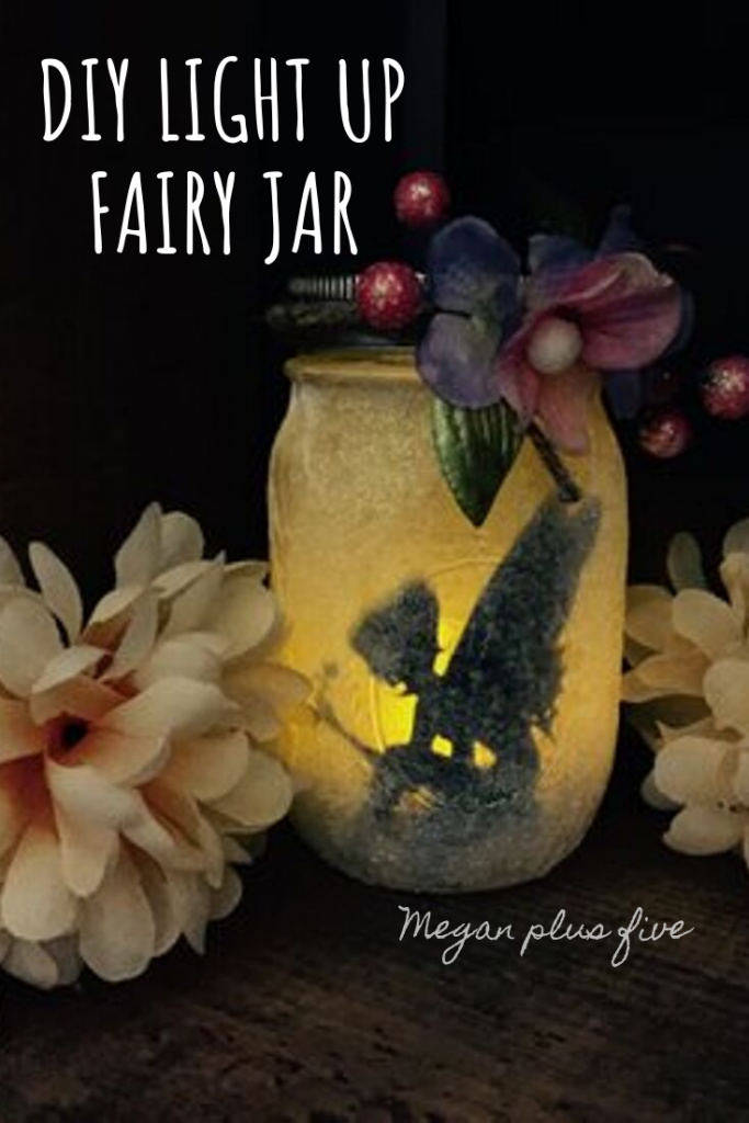 DIY craft tutorial-  how to make your own glittery light up fairy jar lantern from a mason jar. Glowing fairy jar lantern has floral accents, glitter on the outside of the glass jar, warm glowing light from the inside of the jar. Two large flowers on either side of the mason jar. Jar is whimsical looking.