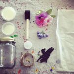 """Materials and supplies needed to make a light up fairy jar. Clean smooth mason jar, twine, iridescent extra fine glitter, container of mod podge, 1/2"""" black tipped sponge brush with wood handle, assorted whimsical fake flowers, fake berry springs, black cardstock cutout of fairy silhouette, a piece of white tissue paper. Canvas drop cloth in the background."""