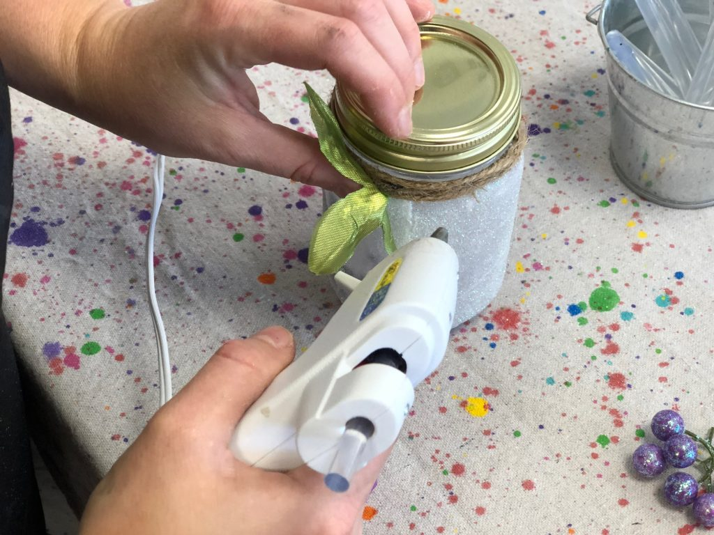 woman is using a hot glue gun to glue floral accents onto twine. She is creating a glittery light up fairy jar lantern from a smooth clear mason jar.