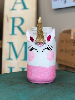 mason jar made to look like a unicorn. Mason jar is painted in white paint with extra fine pink glitter around the bottom of the jar. The jar has a golden unicorn horn with white and pink ears. The unicorn eyelashes are made from black vinyl and it has rosy round pink cheeks.