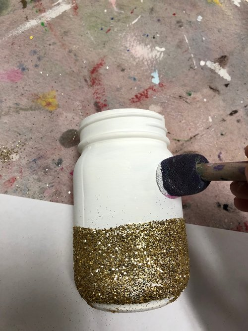 using a round foam dabber to paint cheeks onto a glittery mason jar to make a unicorn mason jar craft. Glitter is gold, glass jar has been painted white.