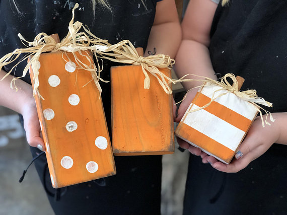 cute mini wooden pumpkins made from 2x4's. Pumpkins are organ with white polka dots, rustic orange, and white pumpkin with orange stripes. Each pumpkin has a raffia bow and wooden stem on the top of the square pumpkins