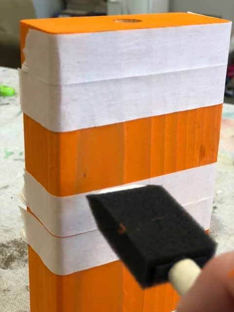 using masking tape to tape off striped areas to paint a 2x4 pumpkin block for rustic fall home decor