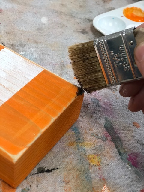woman using a paint brush and antiquing wax to distress a striped orange and white pumpkin for rustic farmhouse fall home decor