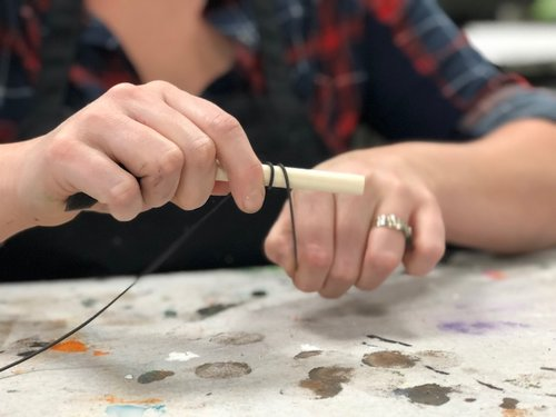 woman is curling rustic wire around a wood paintbrush to curl it for a fall pumpkin accent to the top of the pumpkin.