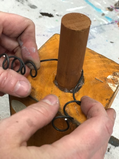 woman is wrapping curly rustic wire around a wooden dowel pumpkin stem for the top of the pumpkin accent