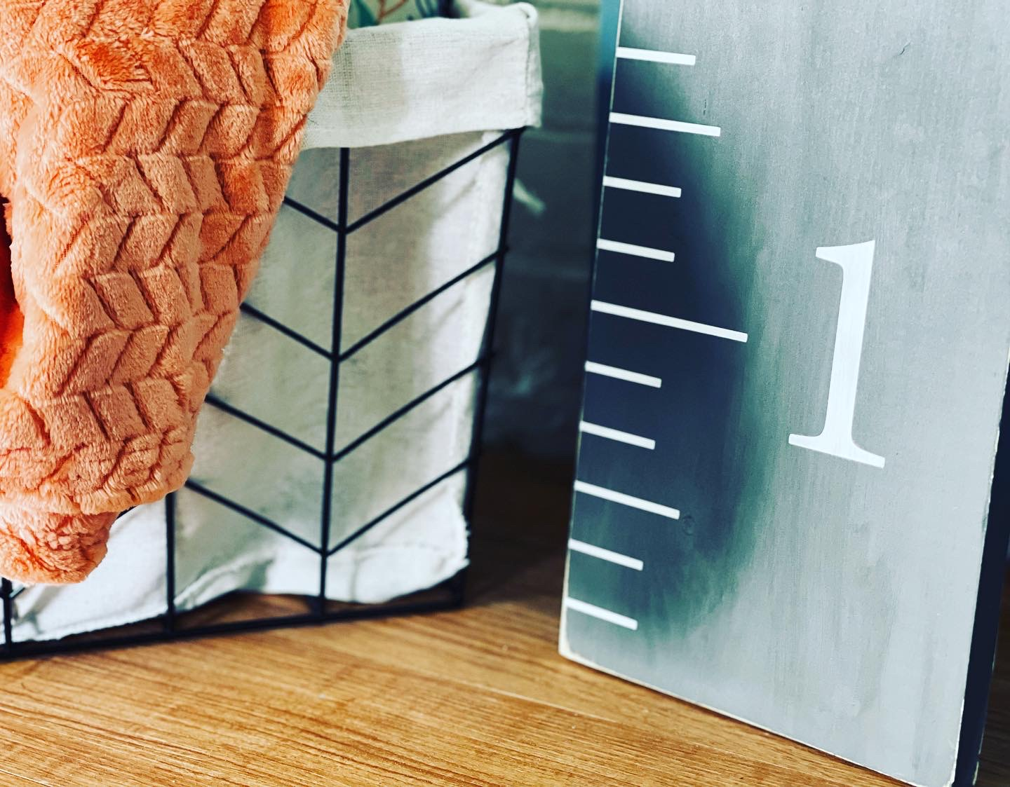gray and white painted wooden growth chart ruler. Metal basket beside the growth chart with a orange colored blanket