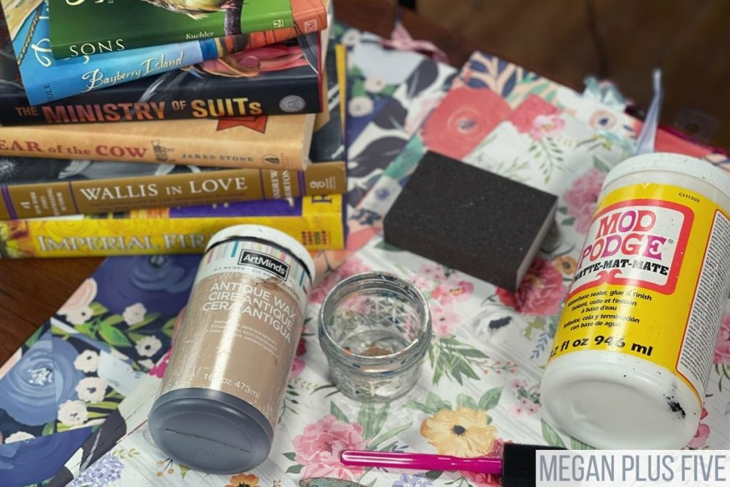 """farmhouse DIY book stack supplies and materials: stack of hardcover books, floral gift bags, matte finish mod podge, antique wax, sanding sponge, 1"""" foam brush"""