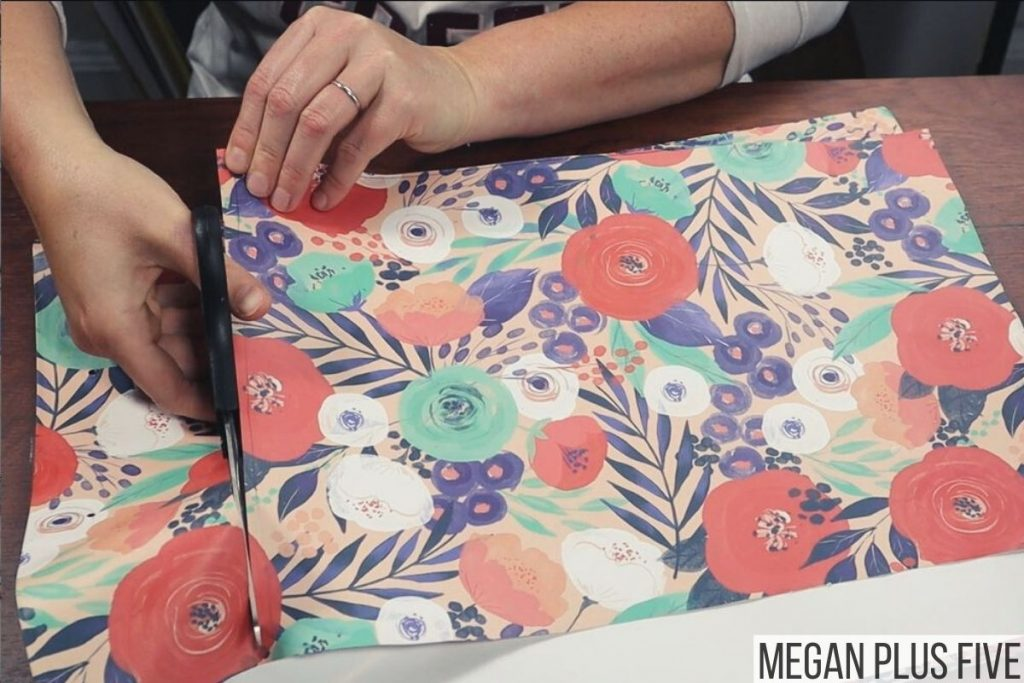 woman is using scissors to cut a floral printed gift bag from the Dollar Tree